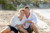 picture of couple sitting beach  - young attractive and beautiful American couple in love sitting on the beach the man hugging woman lying on wet sand smiling happy in romantic summer holidays - JPG