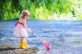 stock photo of rain  - Child playing in a river - JPG
