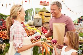 picture of stall  - Family Buying Fresh Vegetables At Farmers Market Stall - JPG