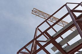 stock photo of tatas  - A top view of a yellow tower crane and red steel structure on a construction site - JPG