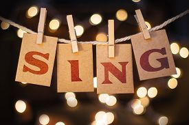 stock photo of glow  - The word SING printed on clothespin clipped cards in front of defocused glowing lights - JPG