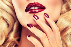 foto of lipstick  - Blonde model with curly Perm hair with Burgundy nails and lipstick - JPG