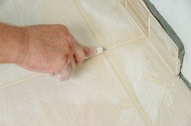 stock photo of grout  - Workers hand smoothing the grout joints between tiles using a rubber stick - JPG