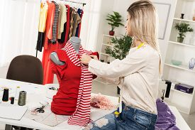picture of dress mannequin  - Young woman fashion designer creates a dress on mannequin. ** Note: Shallow depth of field - JPG