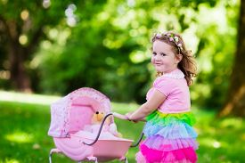stock photo of baby doll  - Little girl pushing toy stroller with bear - JPG