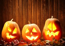 picture of halloween  - Jack o lanterns  Halloween pumpkin face on wooden background and autumn leafs - JPG