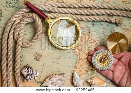poster of Old vintage retro compass magnifying glass on ancient world map. Vintage still life. Travel geography navigation concept background