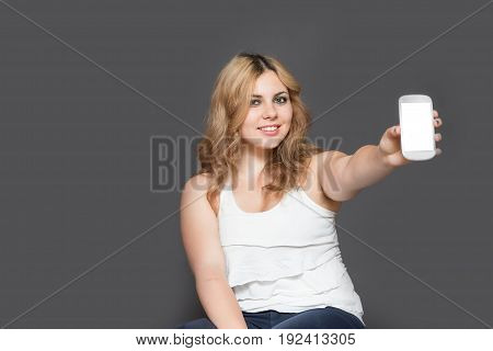 Studio shot of attractive long haired smiling teenage girl showing smart phone with blank touchscreen. All is on the gray background. All potential trademarks and buttons are removed.