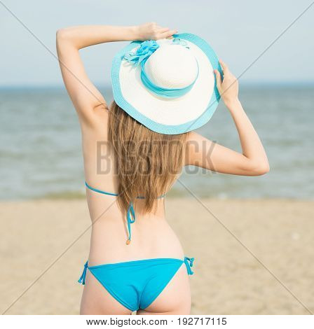 2c03582c87 Young lady sunbathing on a beach. Beautiful woman posing at the summer sand  beach. Outdoor summer portrait of pretty sport ...