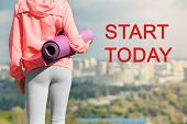 Fitness quotes. Text START TODAY and young woman with mat on cityscape background poster