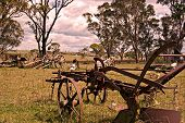 picture of horse plowing  - an old rusting horse drawn plow sits in the farm paddock - JPG