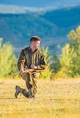 Hunter Khaki Clothes Ready To Hunt Hold Gun Mountains Background. Hunting Shooting Trophy. Hunter Wi poster