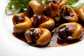 Snails Cooked In Tamarind Sauce With Herbs On A Plate