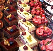 foto of french pastry  - Colorful pastries topped with fruits on display in a French patisserie - JPG