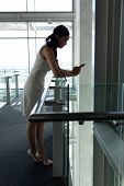 Side view of young businesswoman leaned on the railing and chating on his mobile phone on first floo poster