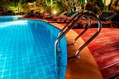 Swimming Pool With Wooden Deck And Stair. Romantic Evening Lighting Setting Near The Pool, Has Lands poster
