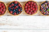 Raspberry And Blueberry Tartlets With Chocolate Ganache, Fresh Berries And Mint Leaves, Selective Fo poster