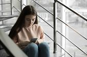 Upset Teenage Girl With Smartphone Sitting On Stairs Indoors. Space For Text poster