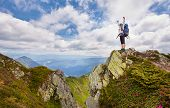 Successful Young Woman Backpacker Open Arms On Mountain Peak poster