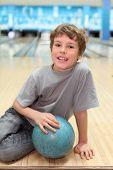Постер, плакат: улыбка счастливый мальчик сидит на полу с синий шар в боулинг клубе