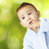 pic of housecoat  - portrait of  an adorable infant with his finger in his mouth wearing a bathrobe - JPG