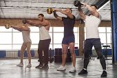 Male Focused Friends Lifting Kettlebells During Workout Session In Gym. High Intense Exercise Class  poster