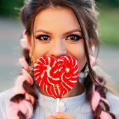 Girl With Lollipop. Beauty Glamour Model Woman With Trendy Hair Holding Pink Sweet Colorful Lollipop poster