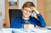 Portrait Of Cute School Kid Boy Wearing Glasses At Home Making Homework. Little Concentrated Child W poster