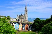 Colorful Row Houses With Towering Cathedral In Background In The Port Town Of Cobh, County Cork, Ire poster