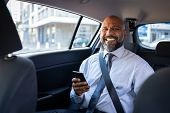 African mature businessman holding smartphone while looking at camera. Successful entrepreneur weari poster