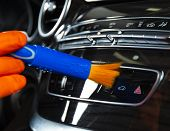 Brush Cleaning Off Dust From The Car Interior Details, Control Panel Of The Dashboard. A Man Cleanin poster