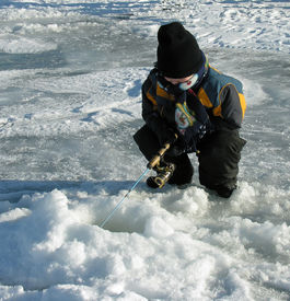 image of ice fishing  - a small boy ice fishing on an alberta lake - JPG