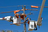 image of utility pole  - Utility workers repair power lines from the safety of a bucket boom - JPG