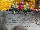 picture of revelation  - silk flowers on a cemetery grave tombstone revelations bible verse - JPG