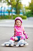 Little roller skater with skates and pink protective equipment on