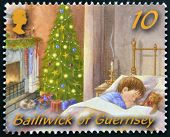 GUERNSEY - CIRCA 2005: A christmas stamp printed in Guernsey shows sleeping child on Christmas Eve c