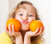 Child with oranges. Happy little girl with fruit at home.