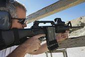 picture of shooting-range  - Man aiming machine gun at firing range - JPG