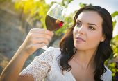 Pretty Mixed Race Young Adult Woman Enjoying A Glass of Wine in the Vineyard.