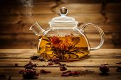 stock photo of teapot  - Glass teapot with blooming tea flower inside against wooden background  - JPG