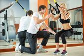 picture of supervision  - Woman doing workout with fitness straps under supervision an personal trainer - JPG