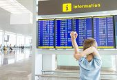 picture of boring  - Rear view of a bored kid crossing his arms and looking panel flight times in the airport - JPG
