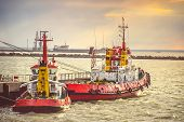 foto of freightliner  - Red Boats in Sea Port transport strait of Kerch in Crimea with sunset sky on background - JPG