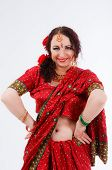 stock photo of namaskar  - european brunette girl in red indian saree with her hands on her hips on gray background in studio - JPG
