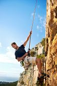 stock photo of mountain-climber  - A rock climber going down a steep mountain with a rope against a blue sky - JPG