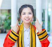 picture of polite girl  - Graduate Thai college girl in academic gown is holding poles and smiling happily for the moment