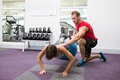picture of personal care  - Personal trainer with client doing push up on exercise ball at the gym - JPG