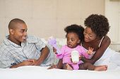 picture of babygro  - Happy parents and baby girl sitting on bed together at home in the bedroom - JPG