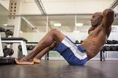 pic of crunch  - Full length side view of muscular man doing abdominal crunches in gym - JPG