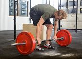 stock photo of jerk  - Full length of fit young man picking barbell in box - JPG